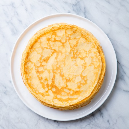 Crepes, thin pancakes on a white plate. Marble background. Copy cpace. Top view. Stock Photo