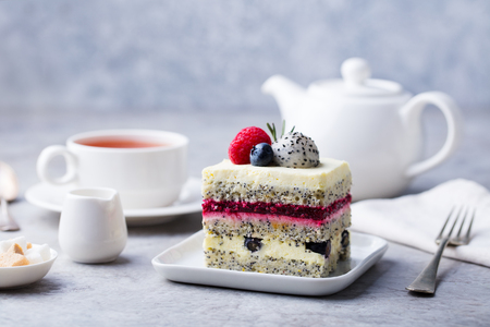 Berry, poppy seed layered cake on white plate. Breakfast concept. Grey background. Copy space.