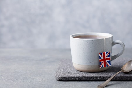 Tea in mug with British flag tea bag label. Grey background. Copy space.