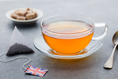 Tea cup with British flag tea bag label. Grey background. Close up. Stok Fotoğraf
