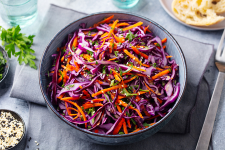 Red cabbage salad. Coleslaw in a bowl. Grey background. Close up. Imagens