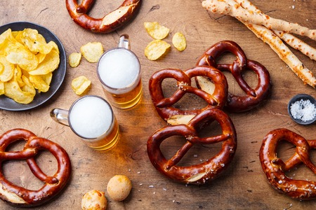 Beer, salted pretzels on wooden table background. Top view. Stock Photo