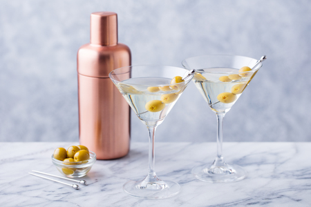 Martini cocktail with green olives, shaker on marble table background. Copy space