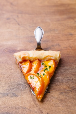Peach galette, pie, cake on a wooden background. Copy space.