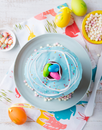 Easter cake with colorful eggs. White wooden background. Top view.