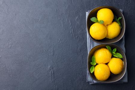 Mango-Eis, tropisches Fruchtsorbet in schwarzer Schüssel auf Schieferhintergrund. Platz kopieren. Ansicht von oben.