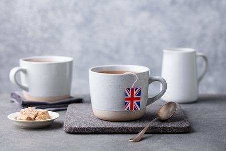Tea in mugs with British flag tea bag label. Grey background. Copy space.