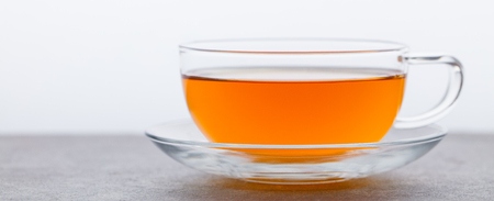 Tea in glass cup. Grey background. Copy space.