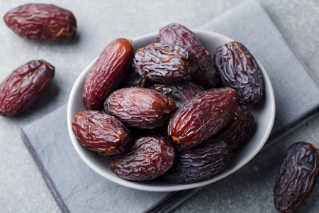 Fresh medjool dates in bowl. Grey background. Close up. Stock Photo