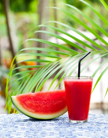 Watermelon fresh juice, smoothie on tropical outdoor background with palm leaves. Copy space. Stock Photo