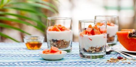 Dessert with papaya, yogurt and granola in glasses. Outdoor background. 스톡 콘텐츠