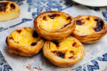 Egg tart, traditional Portuguese dessert, pastel de nata on a plate. Blue textile background. Stock Photo