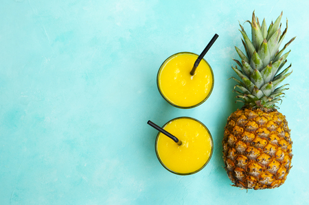 Pineapple with tropical fresh juice, smoothie on blue background. Copy space. Top view. Stock Photo