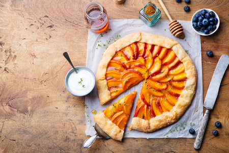 Peach galette, pie, cake with honey and berry on a wooden background. Copy space. Top view.