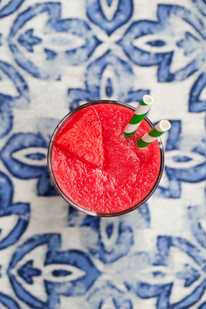 Fresh watermelon juice, smoothie on blue textile background. Top view. Imagens