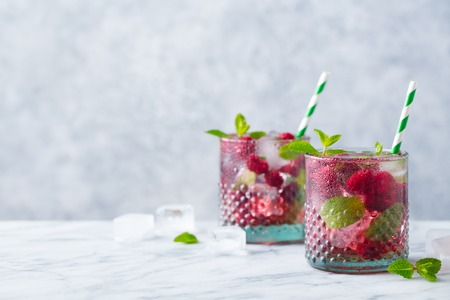 Raspberry cocktail, fizz, lemonade, ice tea with fresh mint on marble background. Copy space. 写真素材