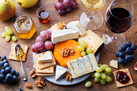 Assortment of cheese, grapes with red and white wine in glasses. Wooden background. Top view.
