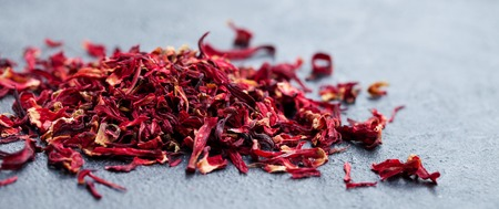 Hibiscus flower tea scattered on grey stone background. Copy space.