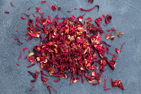 Hibiscus flower tea scattered on grey stone background. Copy space. Top view.