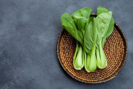 Bok Choy frischer Salat auf Holzplatte. Grauer Hintergrund. Ansicht von oben. Platz kopieren.