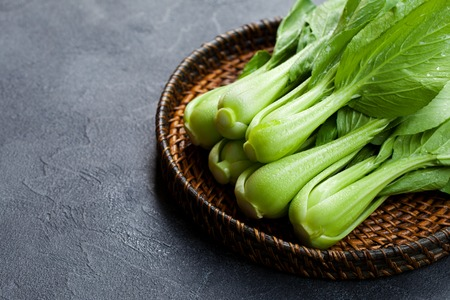 Bok choy fresh salad on wooden plate. Grey background. Copy space. 写真素材