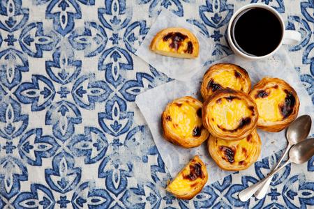 Egg tart, traditional Portuguese dessert, pastel de nata on a parchment paper. Blue background. Top view. Copy space.