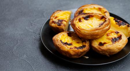 Egg tart, traditional Portuguese dessert, pastel de nata, pasteis on a plate. Grey stone background. Copy space. Stock Photo