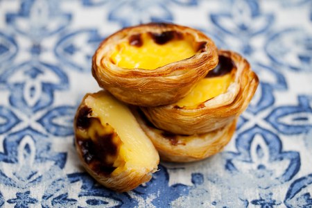 Egg tart, traditional Portuguese dessert, pastel de nata. Blue background. Close up. Stock Photo