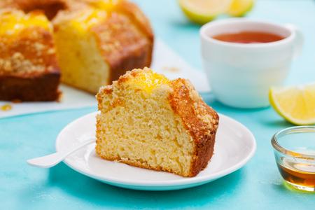 Lemon bundt cake with cup of tea. Blue background. Close up Stock Photo
