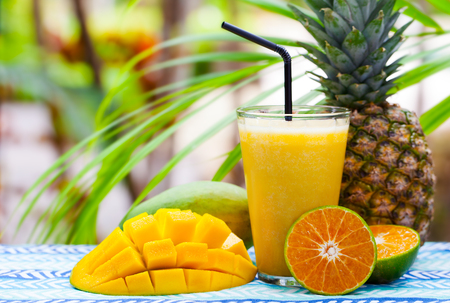 Fresh tropical fruit juice, smoothie in glass on summer outdoor background. Copy space 写真素材