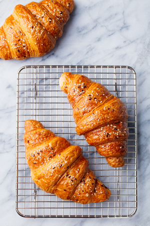 Croissants on cooling rack. Traditional French food. 写真素材