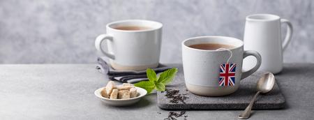 Tea in mugs with British flag tea bag label. Stock Photo