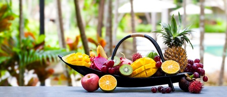 Tropical fruits assortment in wooden boat. Imagens