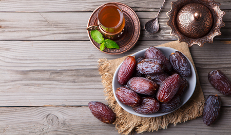 Fresh Medjool Dates in a bowl with tea Stock Photo
