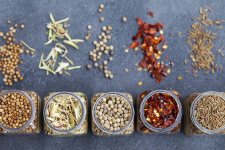 Assortments of spices in jars on grey stone