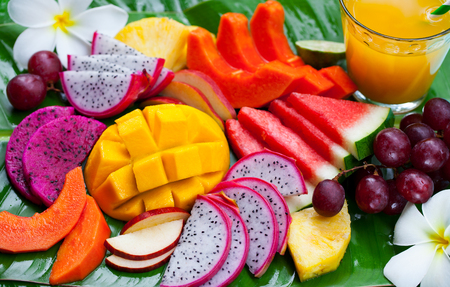 Tropical fruits assortment with fresh juice, palm leaf Imagens