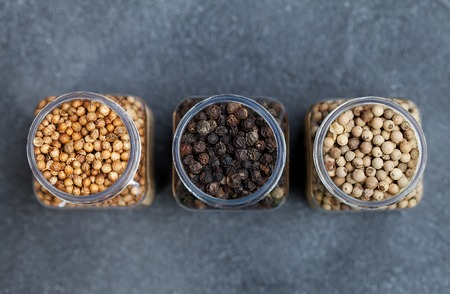 Black, white pepper, peppercorns, coriander seeds in jars