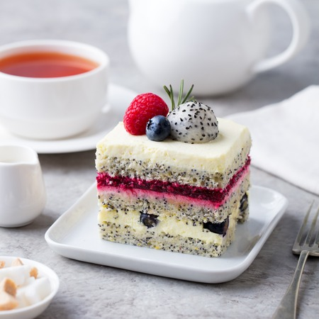 Berry, poppy seed layered cake on white plate. 写真素材