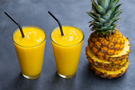 Pineapple with tropical fruit juice, smoothie on dark stone Stock Photo