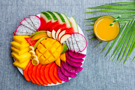Tropical fruits assortment on a white plate with fresh juice, textile grey