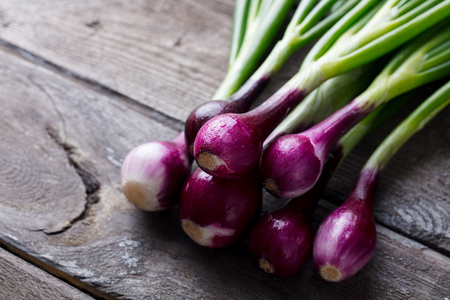 Red onion with fresh green sprouts on wooden Stock Photo