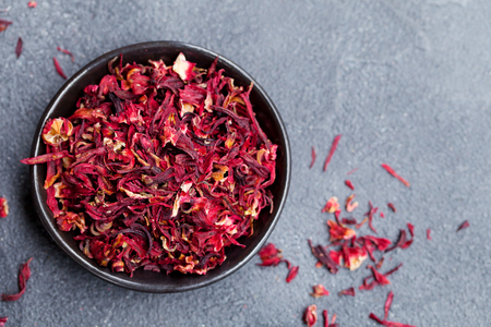 Hibiscus flower tea in black bowl on grey stone