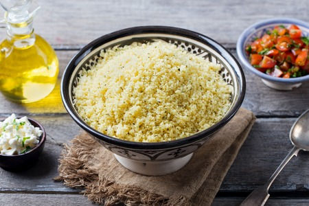 Couscous in bowl with olive oil. Stock Photo