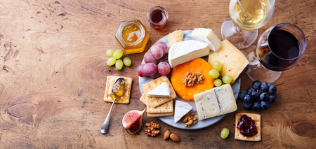 Assortment of cheese, grapes with red and white wine in glasses.