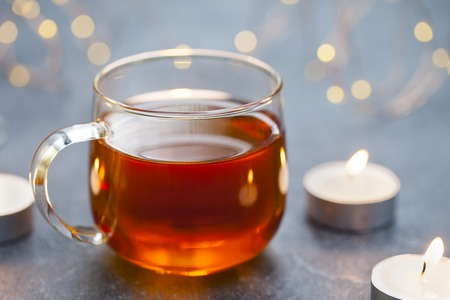 Black tea in glass cup with candles and light garland. Reklamní fotografie - 123097533