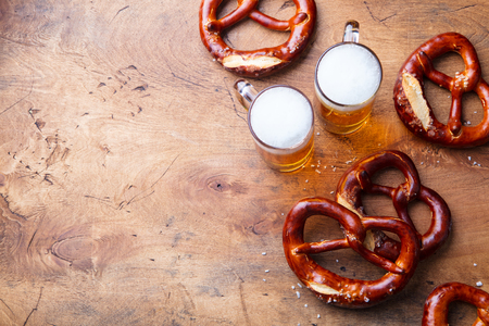 Beer, salted pretzels, potato chips on wooden background. Top view. Copy space. 스톡 콘텐츠