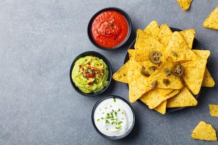 Patatine di nachos su un piatto con salse, varietà di immersione. Sfondo di pietra grigia. Vista dall'alto. Copia spazio. Archivio Fotografico