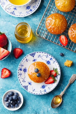Muffin, cupcake with fresh berries on a plate. Blue background. Top view.