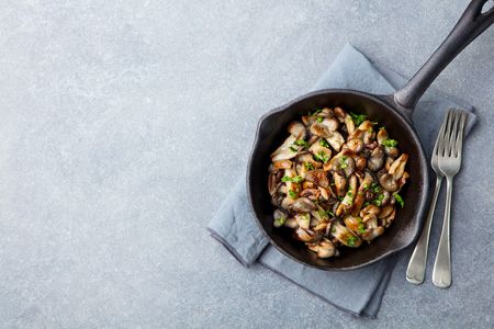 Fried mushrooms with fresh herbs in black cast iron pan. Top view. Copy space. Stock Photo