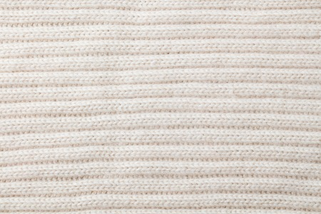 White, beige knitted wool texture background pattern with high resolution. Top view. Copy space.